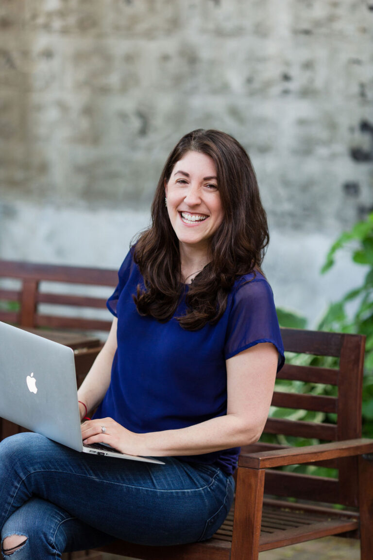 Woman in blue shirt outside sitting on a wooden chair holding a macbook air laptop and laughing