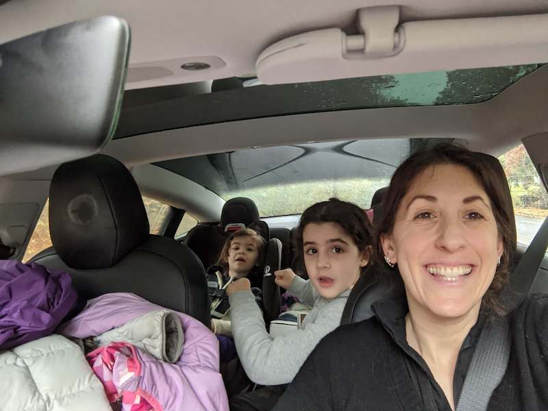 woman with two children in a car
