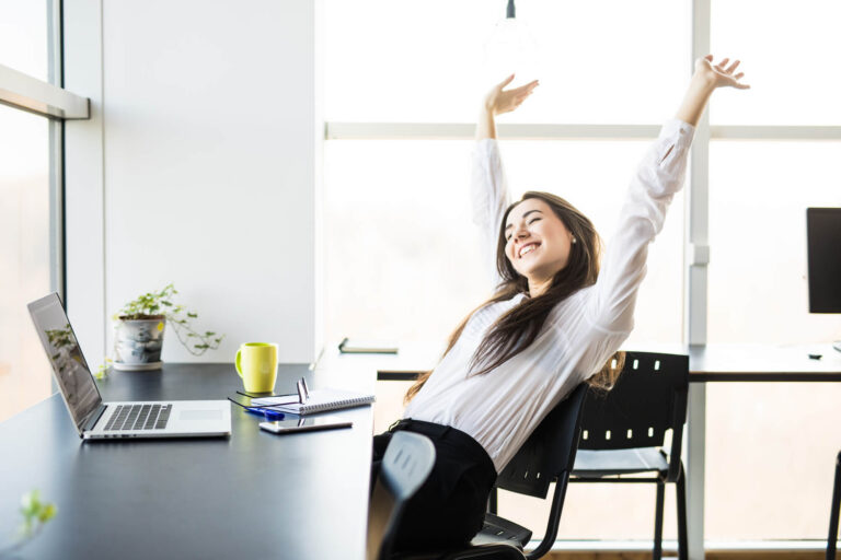 Woman sitting at desk raising her hands in satisfaction that her ConvertKit automations are working correctly